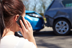 Woman on phone in front of car accident.